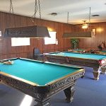 Billiards room with two billiard tables and two poker tables. Wood panel walling and dark wood of the billiard tables and overhanging lights give an rustic, medieval feel to the room.