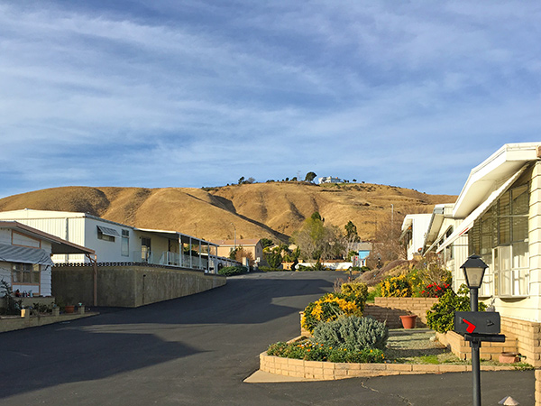 Wide, paved streets lined with manufactured homes and rolling foothills in the background. Well-maintained landscapes make up the front yard of resident's homes.