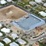 Aerial shot from above which shows the clubhouse in the midst of being built. Construction crews at work digging.