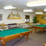 A billiard room with two pool tables with overhead lighting and seating around.