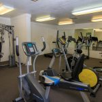 fitness room with elliptical exercise machine, weight lifting machine and treadmills