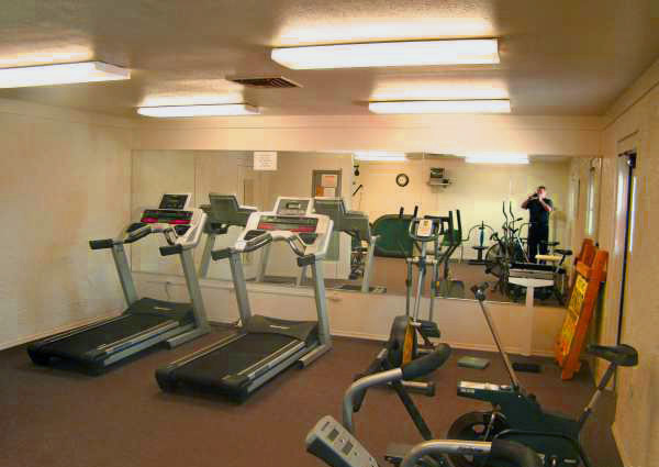 A fitness room with two treadmills, elliptical machine and a stationary bike.