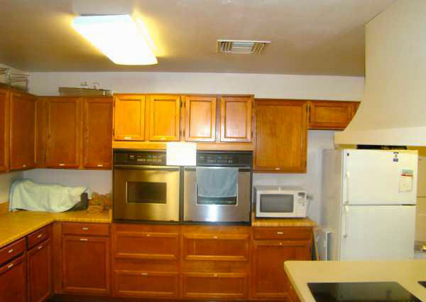 Clubhouse kitchen with wood cabinets, 2 stainless steel ovens, white microwave, and white fridge.