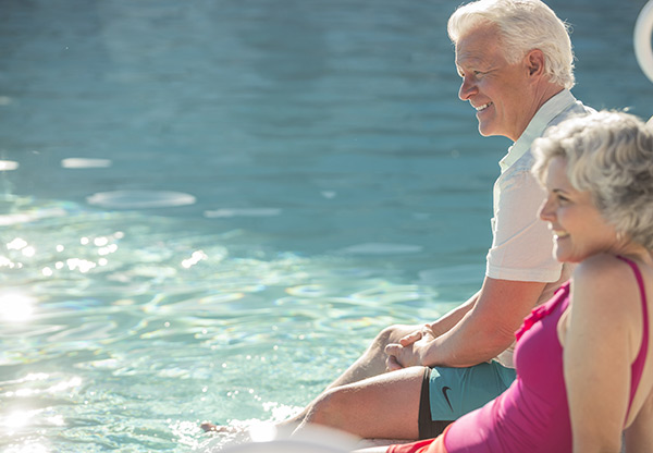 An older couple, man and woman, dipping there feet in the pool.