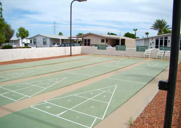 Four outdoor shuffleboard courts with scoreboards.
