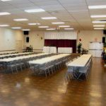 Community room with small stage for events and activities. Long tables and chairs are set up