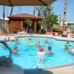 Rose Garden, an active 55 plus community, has heated pool with mature older residents doing water exercises. Pool lounge chairs surround the pool and a wooden covered cabana for shade.