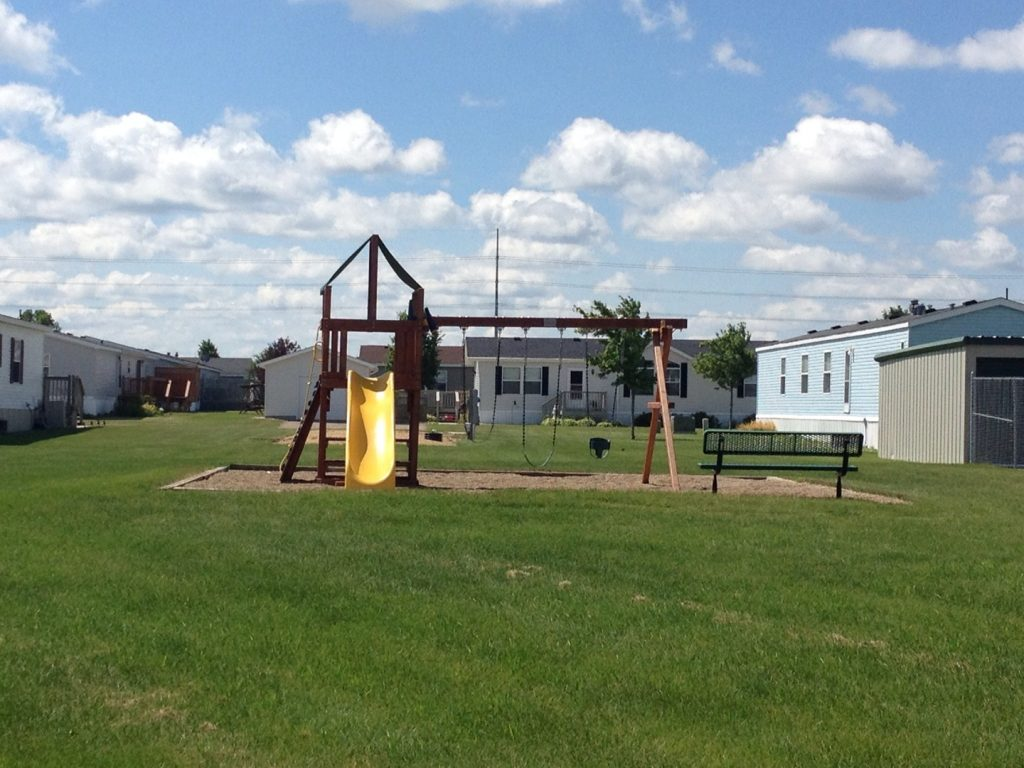 A playground is available with a slide, swings and sandbox. Green grass surrounds the playground for kids to run around on while parents sit on the bench to watch.