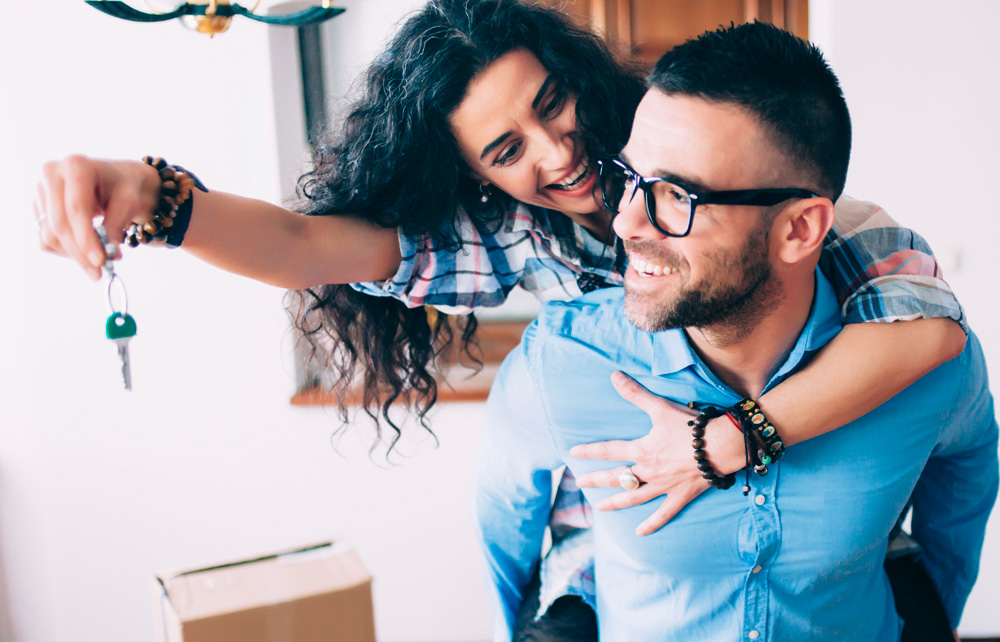 A happy young man and woman celebrate the purchase of a new home. The girl holds a key to the new home while the man smiles.