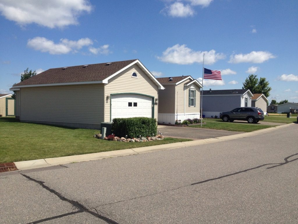 A manufactured home sits on a good size lot and has a garage. Also a shed out back and a flagpole with the American flag.