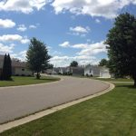 Clean, paved roads throughout the community with lush green trees and full trees.