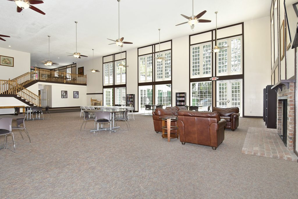 Large community room with tall ceiling and floor to ceiling windows. Tables and chairs to lounge in. Stairs to the second level.