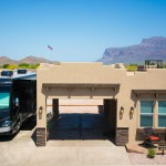 Beautiful beige colored manufactured home with large, connected carport. Beautiful view of the Superstition Mountains in the background.