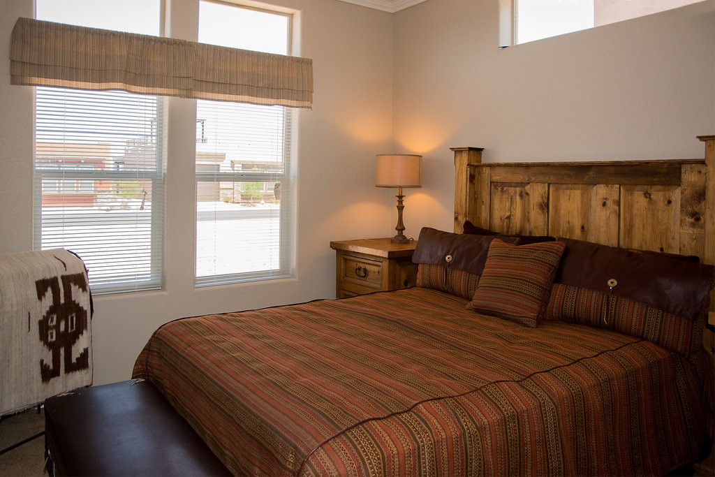 Southwest theme bedroom with rustic wood bed frame and dark red and brown sheets. Large windows that bring in the natural light.