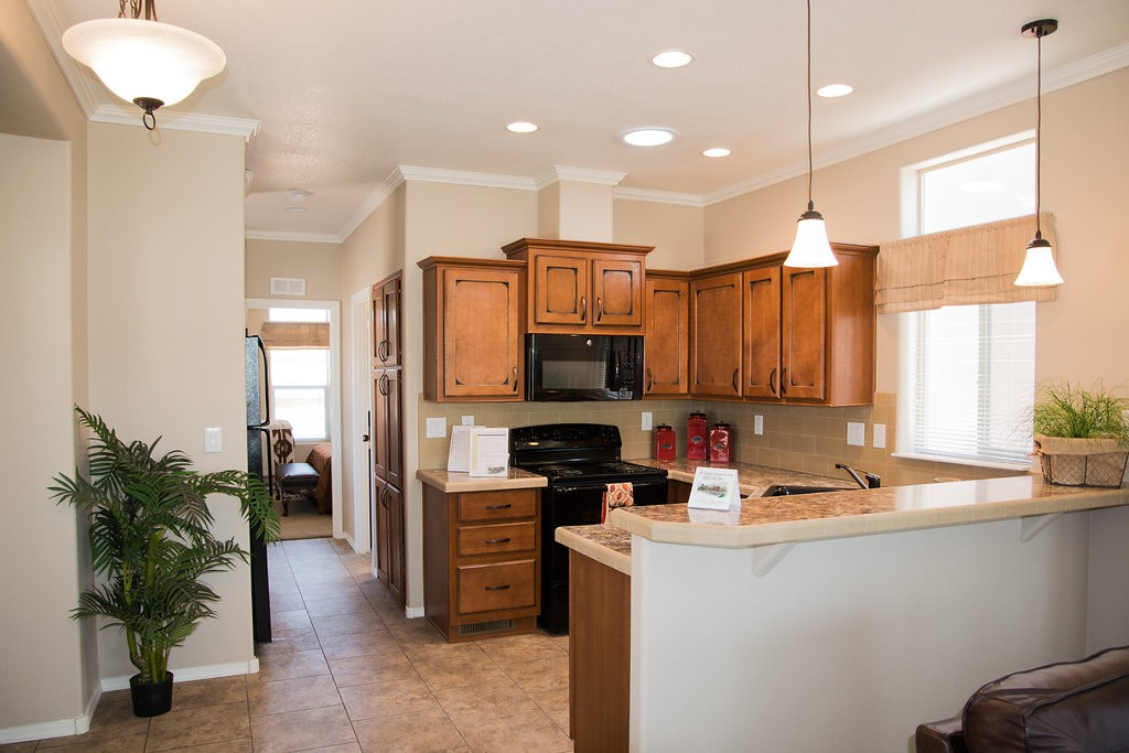 Beautiful, updated kitchen inside home. Wood cabinets, black appliances, and beige granite counter tops. Hanging ceiling lights over small elevated counter for eating.