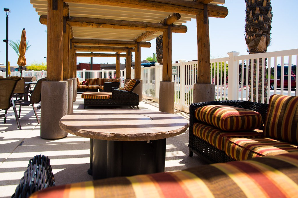 Gazebos lined along one another with a view of the pool. Comfortable seating arrangements for relaxation. Red, brown, and yellow color scheme.