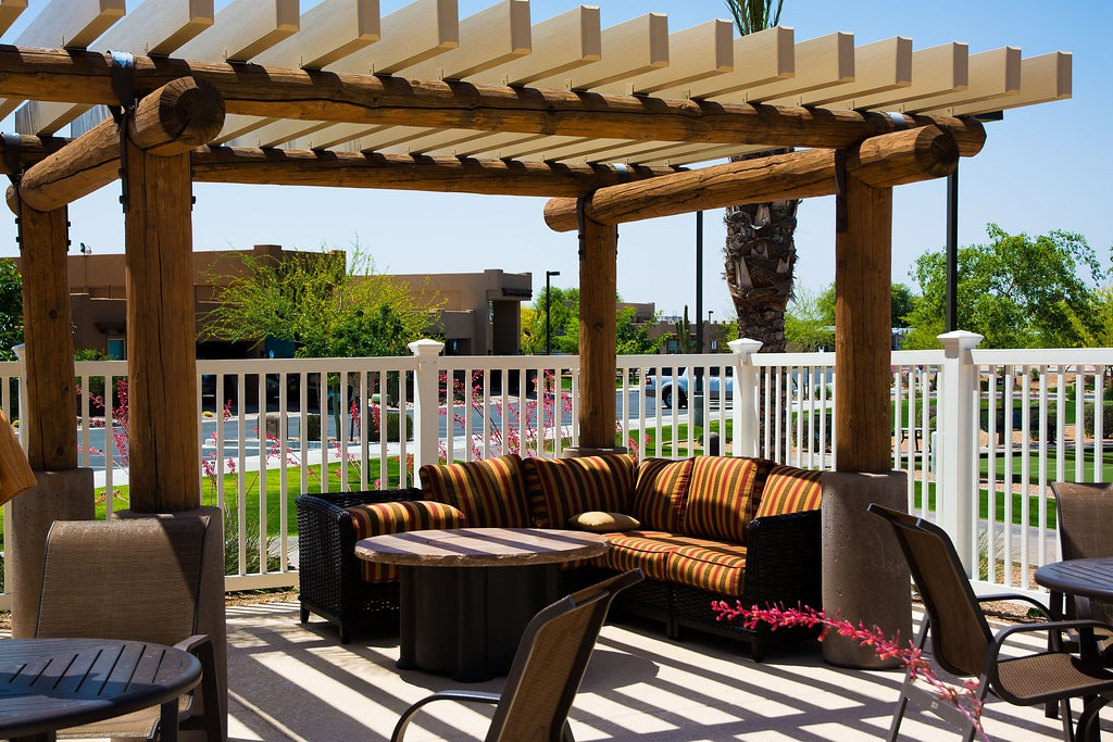 Poolside gazebo with comfortable L shaped outdoor cushioned couch and coffee table.