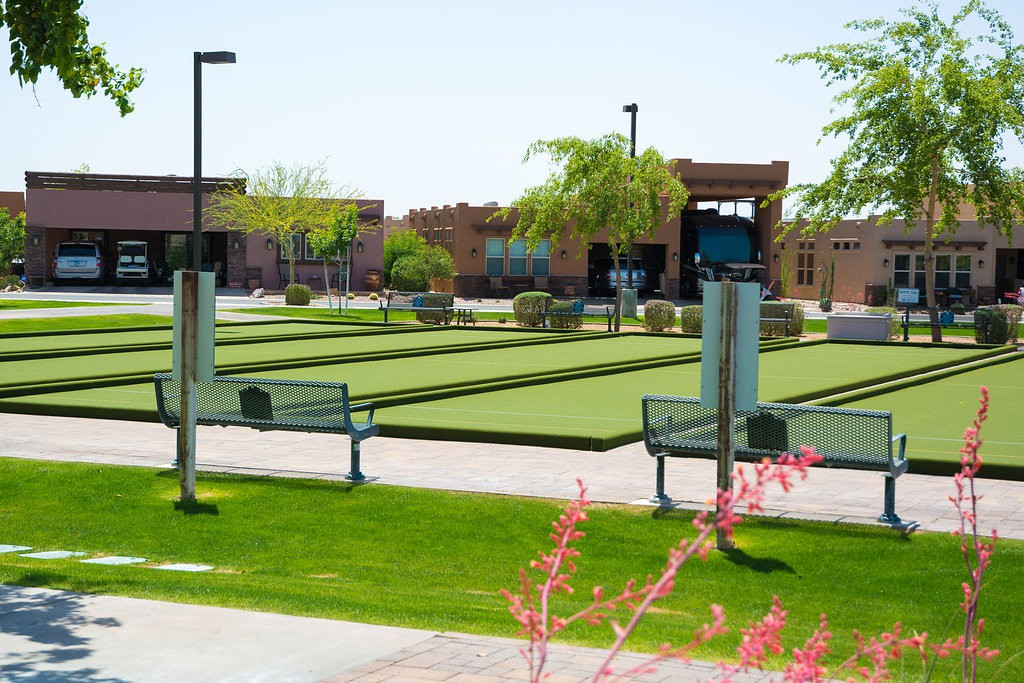 Well-maintained outdoor bocce ball courts lined next to one another. Clean cut, green grass and paved walkways.
