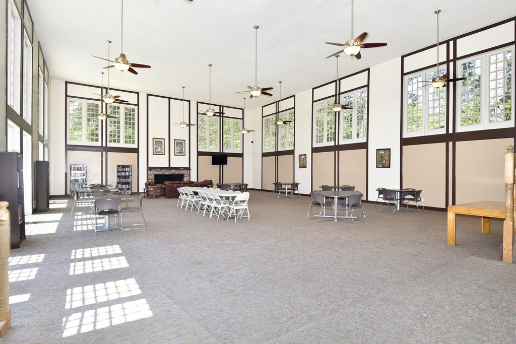 Large community room with very tall ceilings. Windows from floor to ceiling. Many lighted ceiling fans. Tables and chairs to sit at.