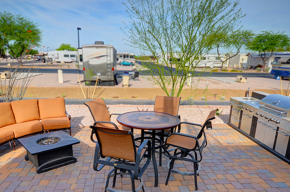 Beautiful outdoor patio with outdoor seating set with orange cushions. Table with four chairs around and matching sofa with a fire-pit in front. Large gas barbeque.