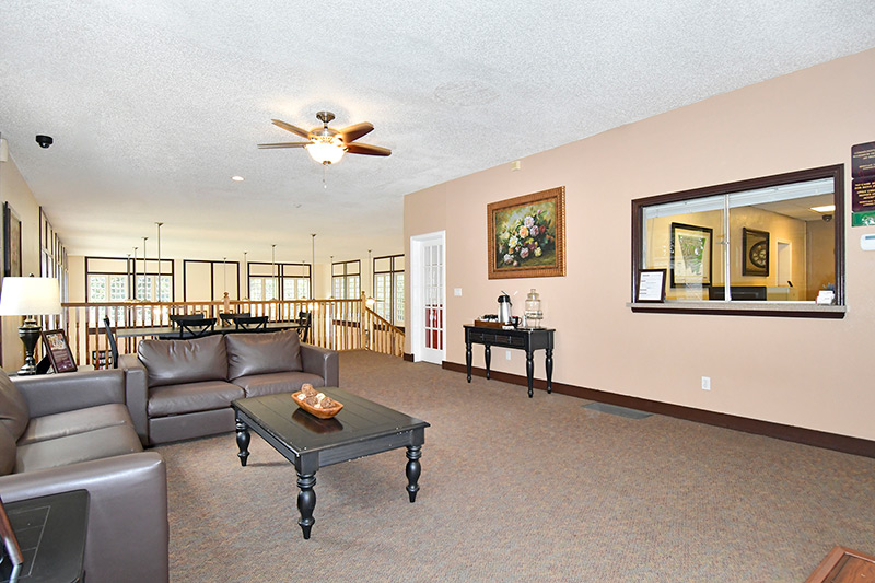 Lounge area on second floor of community center with leather loveseat and couch. Black coffee table. Black console table with coffee and water.