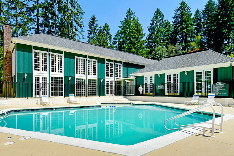 Fenced in swimming pool with lounge chairs next to clubhouse. Very tall green trees landscaped around.
