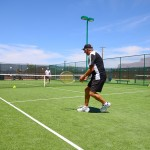 Older male residents playing a game of tennis on one of the four tennis courts on the property.