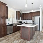 Modern kitchen with open concept. Hardwood flooring in kitchen. Dark wood cabinets and new stainless steel appliances. Kitchen island. Granite countertops. Crown molding top and bottom.