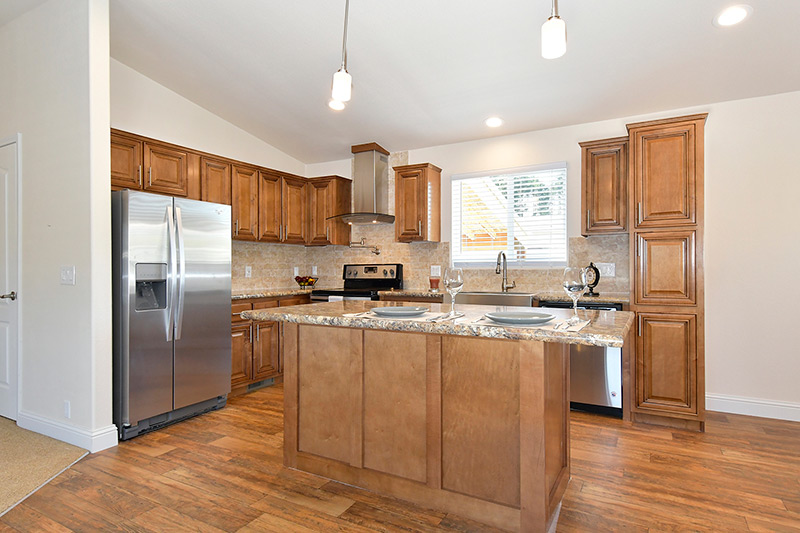 Modern kitchen with open concept. Wood flooring and cabinets. Kitchen island with granite countertops. Stainless steel appliances. Vaulted ceilings.