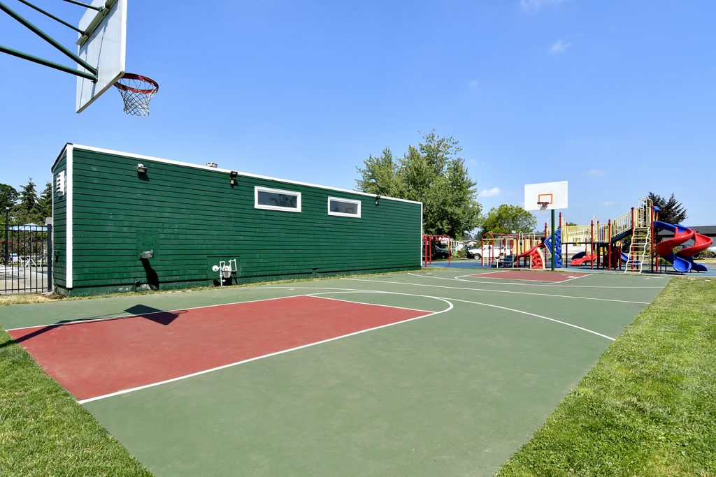 Large outdoor basketball court next to playground.