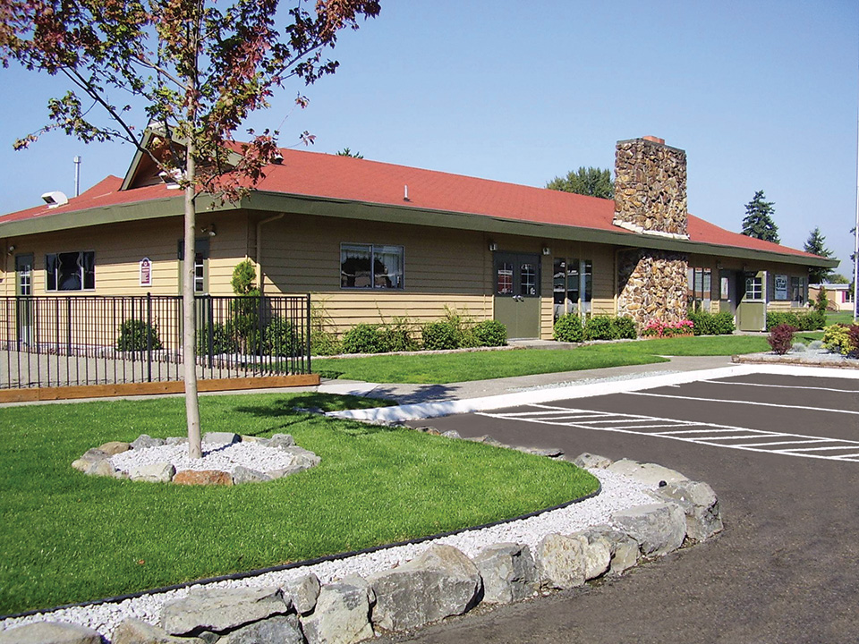 Well-maintained exterior of the community center. Trimmed trees and clean cut grass separated by stones from the paved parking lot.
