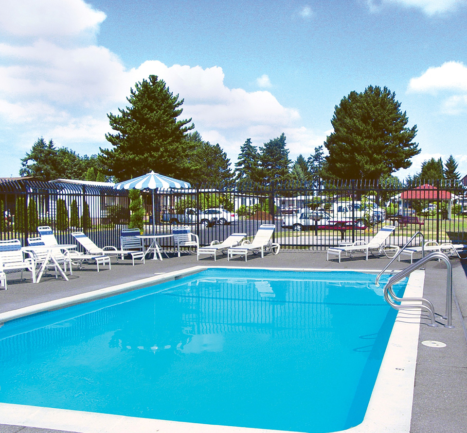 Heated outdoor community pool enclosed by black fencing. Surrounded by blue and white lounge chairs and tables for relaxation.