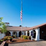 Eldorado Villas Community Center is beautifully landscape with hanging flowers of red and purple and potted plants with mixed flowers. Wood chips and small shrubs. Tall flag pole with American flag. White building with Spanish tile and archways throughout.