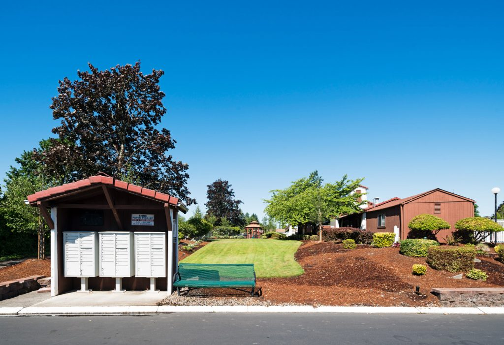 Landscaped beautifully with trimmed grass, full trees and shrubs around the mailboxes. Bench for sitting next to mailboxes.
