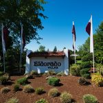 Eldorado Villas, a 55 plus manufactured home community entrance is marked with purple and white flags, small shrubs, and white sign with Eldorado Villas name. Green trees in the background.