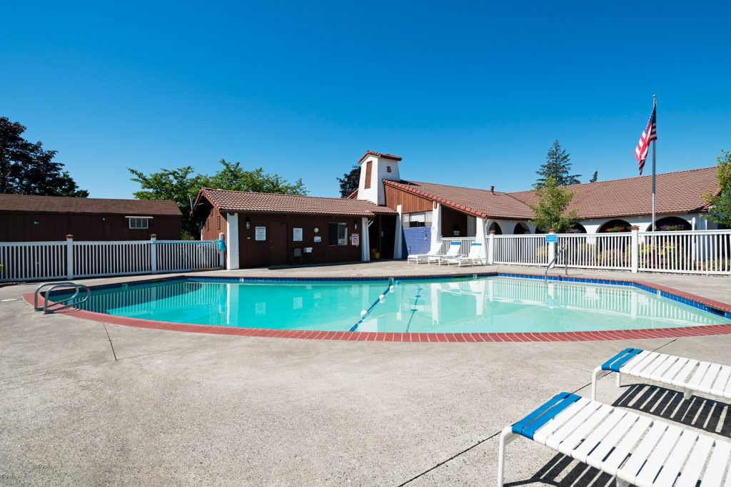 Swimming pool with lounge chairs. American flag flies high on flagpole.