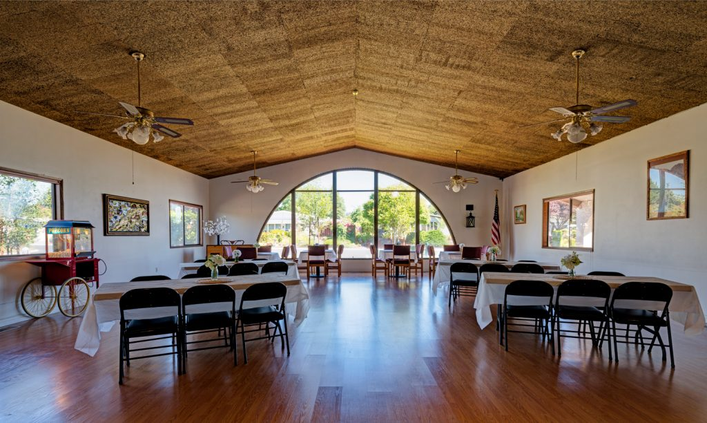 A meeting room that is utilized for events. Set up with tables that are tableclothed and chairs. Popcorn machine and American flag in the corner. Arched window that looks out into the community.