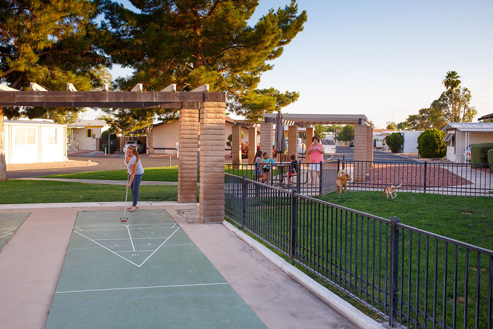 Woman plays shuffleboard next to fenced in dog park while dogs run free and a family watches on from the picnic benches