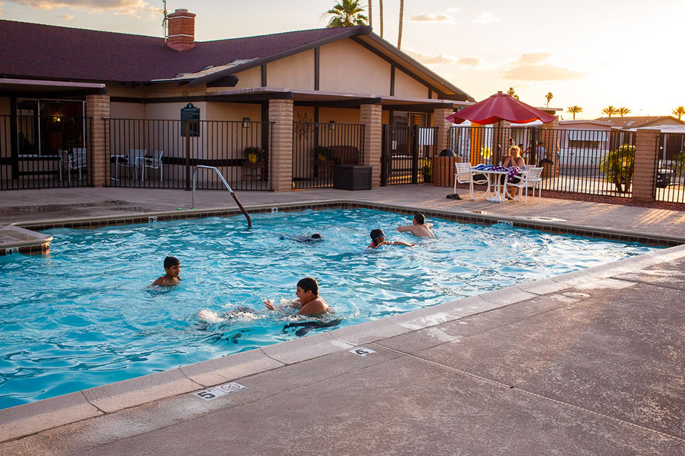 Glendale Cascade swimming pool with family swimming at dusk and clubhouse in the background