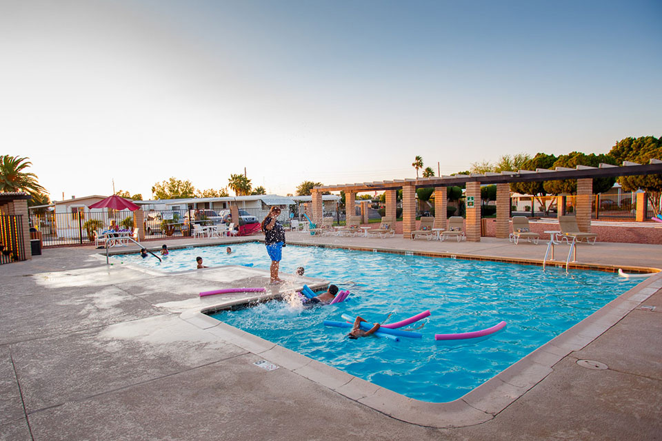 Glendale Cascade, an all age community, with kids splashing around in the pool enjoying the pool floaties while a mother watches on. lounge chairs scattered around the pool.