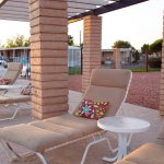 cushioned pool lounge chairs with small pillows and table surround the pool for relaxing.