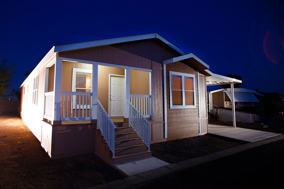 A manufactured home with the porch light on at night