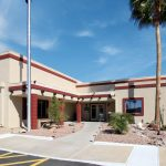 New clubhouse surrounded by flagpole and desert scenery and palm trees