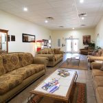 The clubhouse offers a media room with plush couches and tables to sit and enjoy the magazines available along with a free standing popcorn machine to curb your appetite. Jewelry that was crafted by residents is showcased in a glass cabinet that is stored up against a wall.