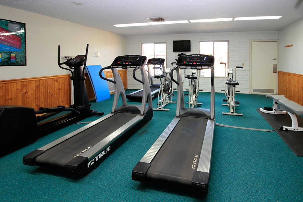 fitness room with treadmills, bicycles, elliptical machine, TV, and bench