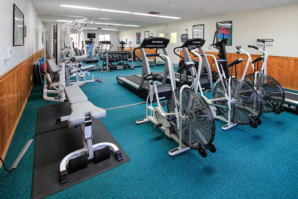 Well equipped fitness room with free weights, treadmills, bicycles, bench, yoga ball and mats and scale