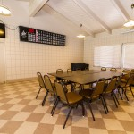 Portion of the community hall provides an inclusive table with surrounding chairs and Bingo board for residents to enjoy a game of Bingo.