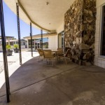 Exit the community hall to enter the outdoor patio and courtyard. Enjoy time under the sun or under the covered patio.