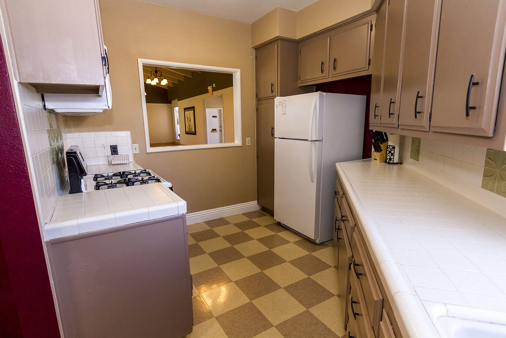Community center kitchen with checkered flooring, light brown cabinets, and white counter-tops. Includes all white fridge, stove, microwave and open window connecting to community hall.