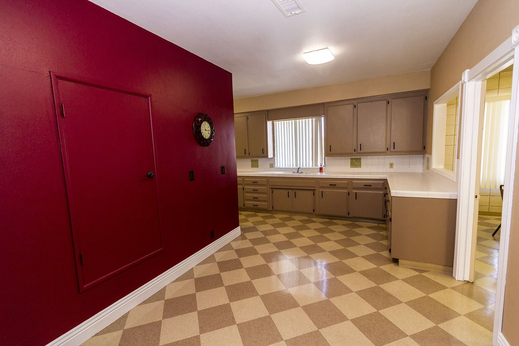Spacious kitchen provides enough counter-space for food preparation. Beautiful dark-red wall creates a warm, home feel.